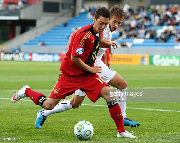 Mesut Oezil of Germany and Domenico Criscito of Italy battle for the ball during the UEFA European U21 Championship Semi Final match between Italy...