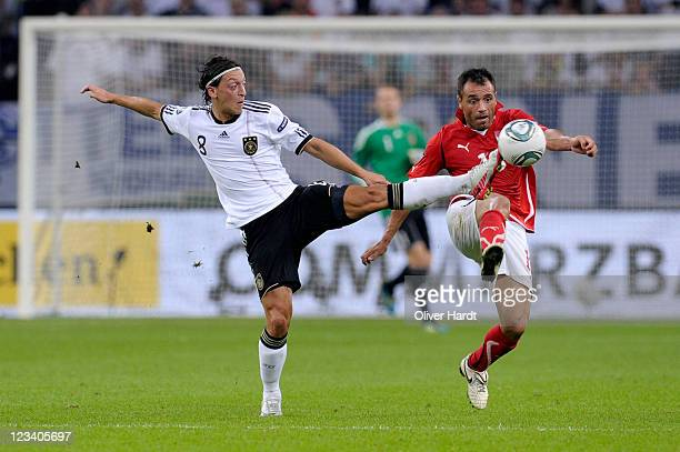 Mesut Oezil of Germany and Ekrem Dag of Austria battle for the ball during the UEFA EURO 2012 qualifying match between Germany and Austria at...