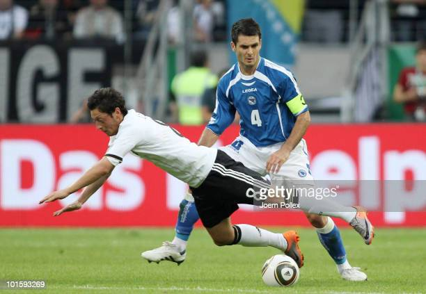 Mesut Oezil of Germany and Emir Spahic of Bosnia-Herzegovina battle for the ball during the international friendly match between Germany and...