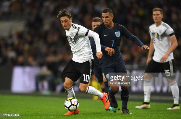 Mesut Oezil of Germany and Jake Livermore of England battle for possession during the International friendly match between England and Germany at...