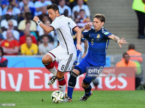 Mesut Oezil of Germany and Lucas Biglia of Argentina compete for the ball during the 2014 FIFA World Cup Brazil Final match between Germany and...