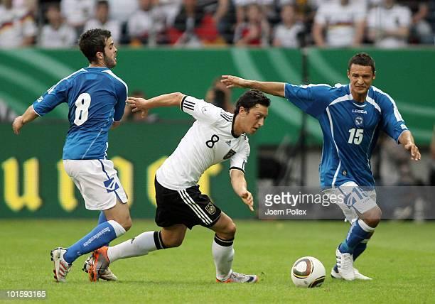 Mesut Oezil of Germany and Miralem Pjanic as well as Sejad Salihovic of BosniaHerzegovina battle for the ball during the international friendly match...