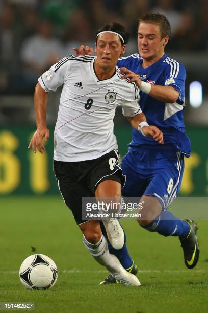Mesut Oezil of Germany battles for the ball with Hallur Hansson of Faeroe Islands during the FIFA 2014 World Cup Qualifier group C match between...