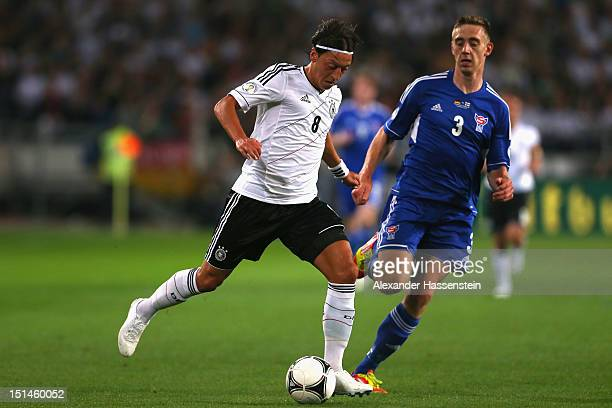 Mesut Oezil of Germany battles for the ball with Pol Johannus Justinusen of Faeroe Islands during the FIFA 2014 World Cup Qualifier group C match...
