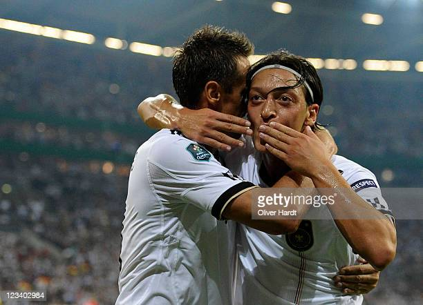 Mesut Oezil of Germany celebrates his second goal with Miroslav Klose during the UEFA EURO 2012 qualifying match between Germany and Austria at...