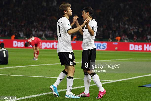 Mesut Oezil of Germany celebrates his team's second goal with team mate Thomas Mueller during the EURO 2012 group A qualifier match between Germany...