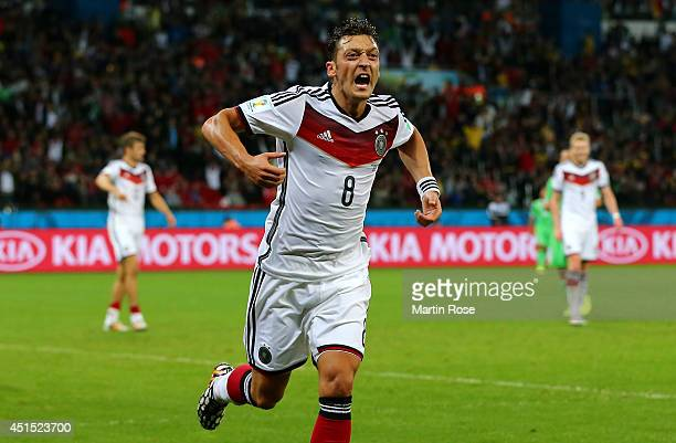 Mesut Oezil of Germany celebrates scoring his team's second goal in extra time during the 2014 FIFA World Cup Brazil Round of 16 match between...
