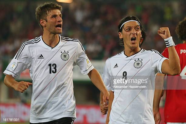 Mesut Oezil of Germany celebrates scoring the 2nd team goal with his team mate Thomas Mueller during the FIFA 2014 World Cup Qualifier group C match...