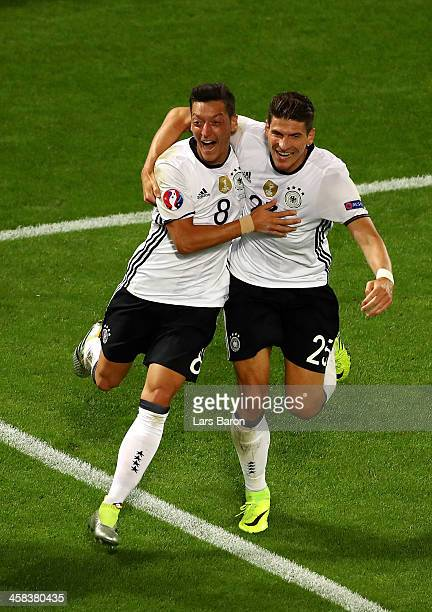 Mesut Oezil of Germany celebrates scoring the opening goal with his team mate Mario Gomez during the UEFA EURO 2016 quarter final match between...