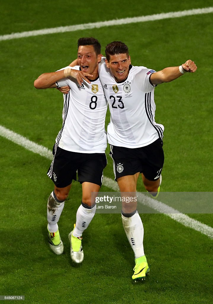 Mesut Oezil (L) of Germany celebrates scoring the opening goal with his team mate Mario Gomez (R) during the UEFA EURO 2016 quarter final match between Germany and Italy at Stade Matmut Atlantique on July 2, 2016 in Bordeaux, France.