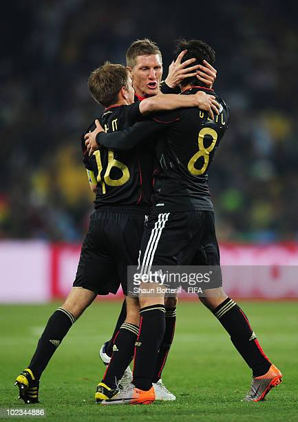 Mesut Oezil of Germany celebrates scoring with Bastian Schweinsteiger and Philipp Lahm of Germany during the 2010 FIFA World Cup South Africa Group D...