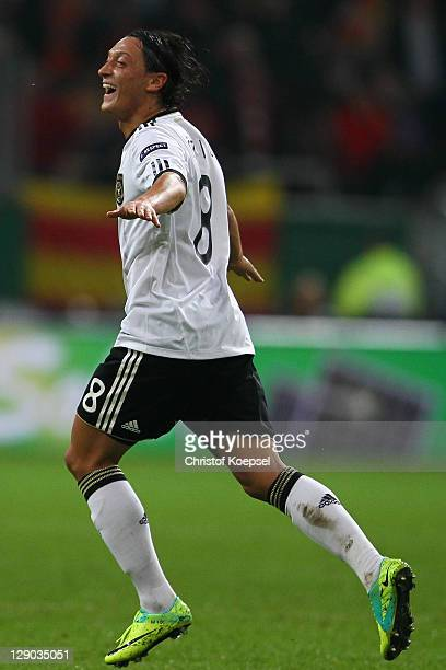 Mesut Oezil of Germany celebrates the first goal during the UEFA EURO 2012 Group A qualifying match between Germany and Belgium at EspritArena on...