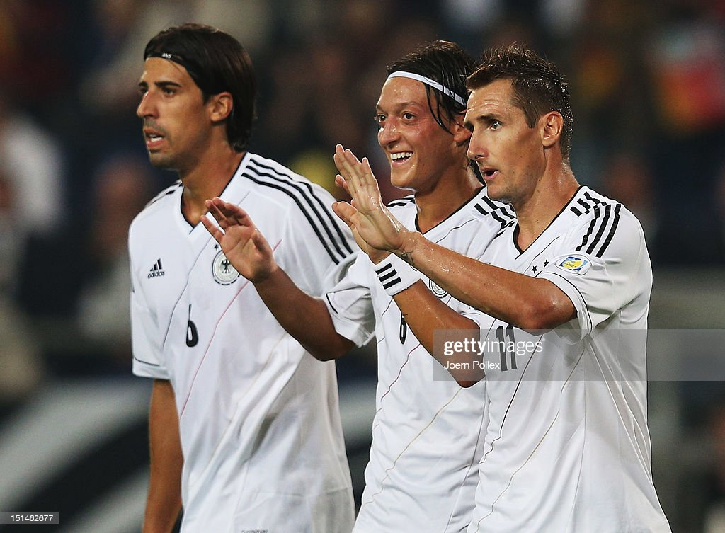 Mesut Oezil (C) of Germany celebrates with his team mates Miroslav Klose (R) and Sami Khedira after scoring his team's third goal the FIFA 2014 World Cup Qualifier group C match between Germany and Faeroe Islands at AWD Arena on September 7, 2012 in Hannover, Germany.