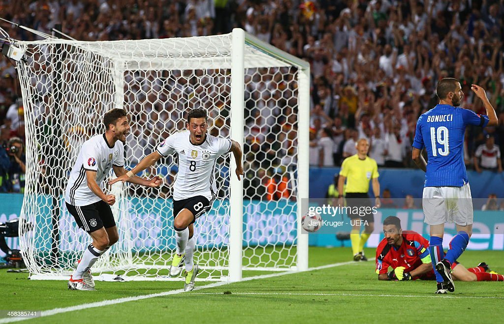 Mesut Oezil of Germany (8) celebrates wtih Jonas Hector (3) as he scores their first goal during the UEFA EURO 2016 quarter final match between Germany and Italy at Stade Matmut Atlantique on July 2, 2016 in Bordeaux, France.