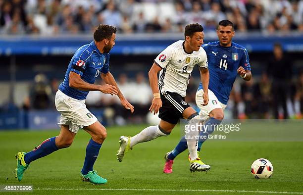 Mesut Oezil of Germany competes for the ball against Andrea Barzagli and Stefano Sturaro of Italy during the UEFA EURO 2016 quarter final match...