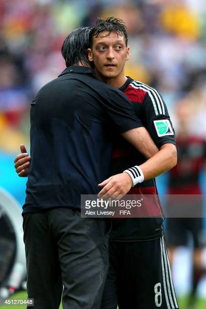 Mesut Oezil of Germany hugs with head coach Joachim Loew of Germany as being replaced during the 2014 FIFA World Cup Brazil Group G match between USA...