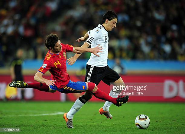 Mesut Oezil of Germany in action against Xabi Alonso of Spain during the 2010 FIFA World Cup South Africa Semi Final match between Germany and Spain...