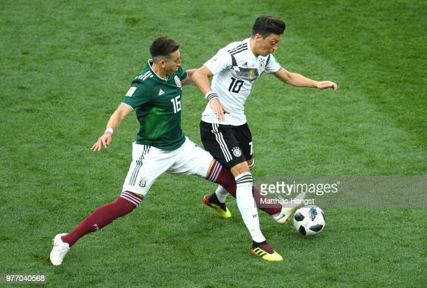 Mesut Oezil of Germany is challenged by Hector Herrera of Mexico during the 2018 FIFA World Cup Russia group F match between Germany and Mexico at...
