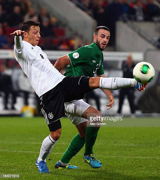 Mesut Oezil of Germany is challenged by Marc Wilson of Ireland during the FIFA 2014 World Cup Group C qualifiying match between Germany and Republic...