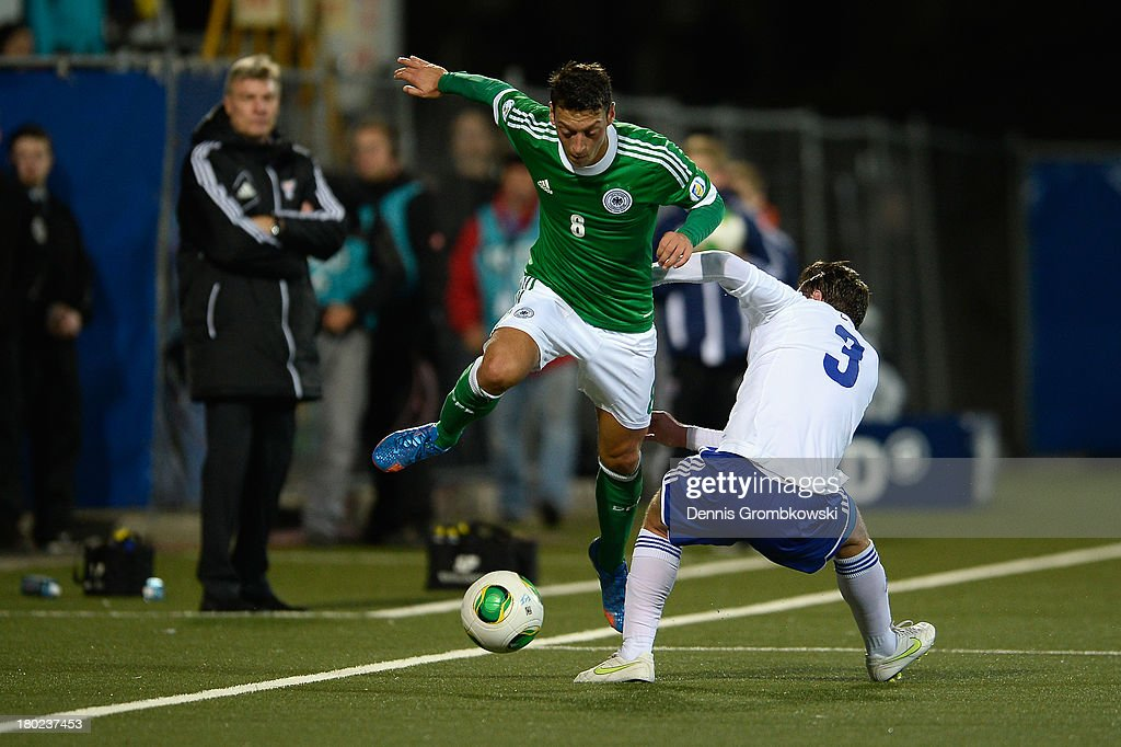 Mesut Oezil of Germany is challenged by Viljormur Davidsen of Faeroe Islands during the FIFA 2014 World Cup Qualifier match between Faeroe Islands and Germany on September 10, 2013 in Torshavn, Denmark.