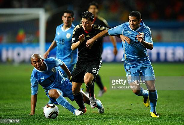 Mesut Oezil of Germany is challenged by Walter Gargano of Uruguay during the 2010 FIFA World Cup South Africa Third Place Playoff match between...