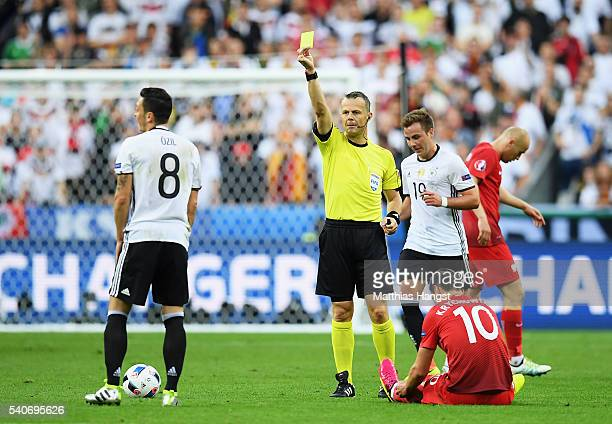 Mesut Oezil of Germany is shown a yellow card by referee Referee Bjorn Kulpers after fouling Grzegorz Krychowiak of Poland during the UEFA EURO 2016...