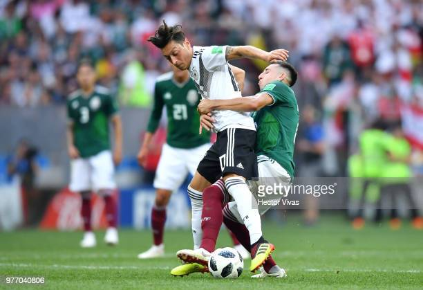 Mesut Oezil of Germany is tackled by Hector Herrera of Mexico during the 2018 FIFA World Cup Russia group F match between Germany and Mexico at...