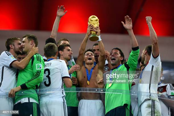 Mesut Oezil of Germany lifts the World Cup to celebrate with his teammates during the award ceremony after the 2014 FIFA World Cup Brazil Final match...