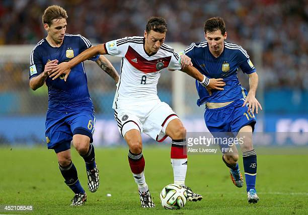 Mesut Oezil of Germany Lucas Biglia and Lionel Messi of Argentina compete for the ball during the 2014 FIFA World Cup Brazil Final match between...