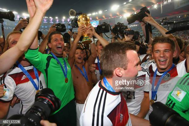 Mesut Oezil of Germany raises the trophy with goalkeeper Roman Weidenfeller of Germany and teammates after defeating Argentina 10 in extra time...