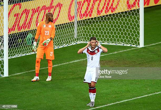 Mesut Oezil of Germany reacts as Rais M'Bolhi of Algeria looks on during the 2014 FIFA World Cup Brazil Round of 16 match between Germany and Algeria...