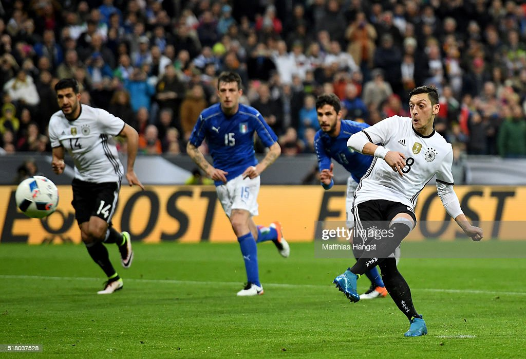 Mesut Oezil of Germany scores his teams fourth goal from the penalty spot during the International Friendly match between Germany and Italy at Allianz Arena on March 29, 2016 in Munich, Germany.