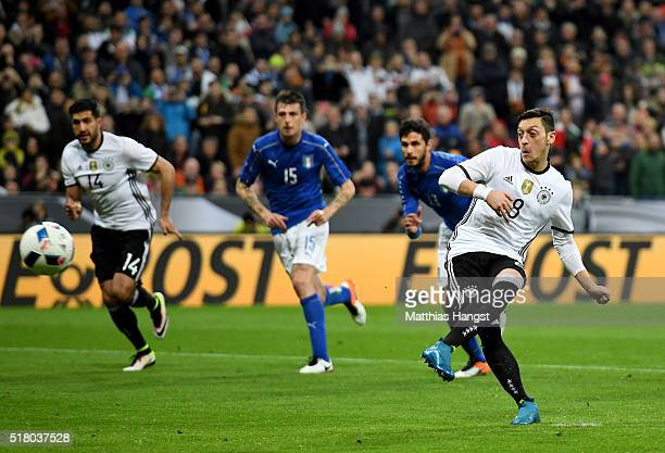 Mesut Oezil of Germany scores his teams fourth goal from the penalty spot during the International Friendly match between Germany and Italy at...