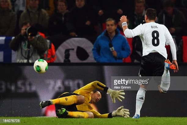 Mesut Oezil of Germany scores his team's third goal against goalkeeper David Forde of Ireland during the FIFA 2014 World Cup Group C qualifiying...
