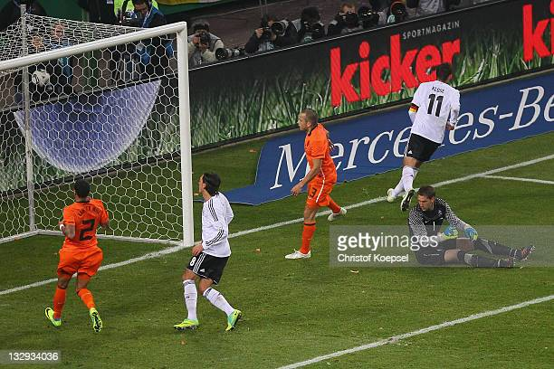 Mesut Oezil of Germany scores the third goal against Gregory van der Wiel Johnny Heitinga and Marteen Stekelenburg of Netherlands during the...