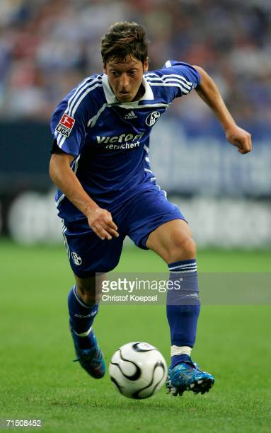Mesut Oezil of Schalke runs with the ball during the Ebbe Sand farewell match between Ebbe Sand Team and FC Schalke 04 at the Veltins Arena on July...