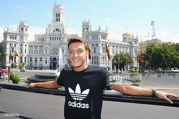 Mesut Oezil pose in font of the City hall at 'Plaza de Cibeles' during a city tour after the adidas presentation of the new campaign Welcoming Mesut...