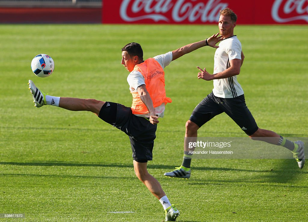 Mesut Oezil stretches for the ball ahead of Benedikt Hoewedes during a Germany training session ahead of the UEFA EURO 2016 at Ermitage Evian on June 7, 2016 in Evian-les-Bains, France. Germany's opening match at the European Championship is against Ukraine on June 12.