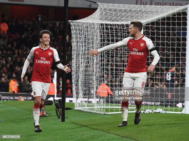 Mesut Ozil and Aaron Ramsey celebrate the 3rd Arsenal goal scored by Alexis Sanchez during the Premier League match between Arsenal and Huddersfield...
