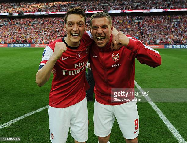 Mesut Ozil and Lukas Podolski of Arsenal celebrate after the FA Cup Final between Arsenal and Hull City at Wembley Stadium on May 17, 2014 in London,...