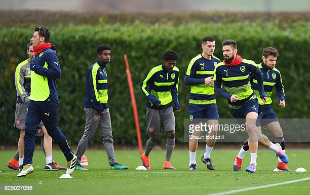 Mesut Ozil and Olivier Giroud perform drills with team mates during an Arsenal training session on the eve of their UEFA Champions League match...