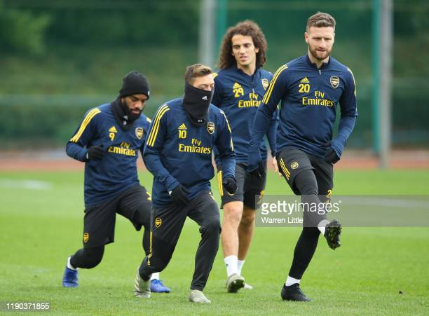 Mesut Ozil and Shkodran Mustafi warm up during an Arsenal training session on the eve of their UEFA Europa League match against Eintracht Frankfurt...