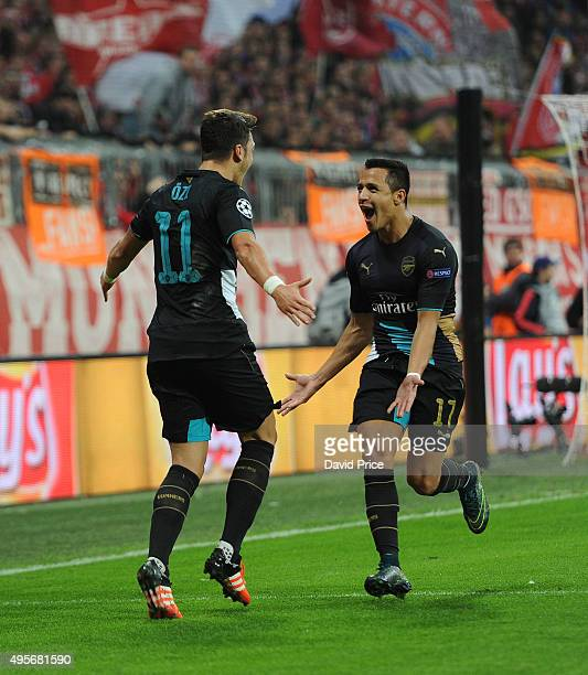 Mesut Ozil celebrates scoring a goal that is later ruled out with Alexis Sanchez of Arsenal during the match between Bayern Munich and Arsenal on...