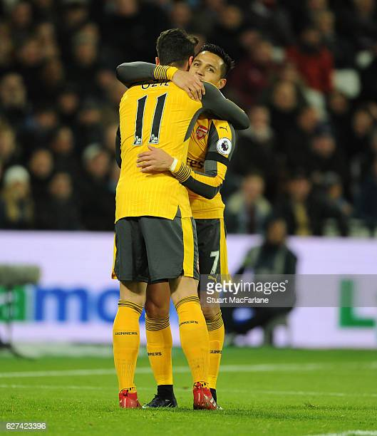 Mesut Ozil celebrates scoring the 1st Arsenal goal with Alexis Sanchez during the Premier League match between West Ham United and Arsenal at London...