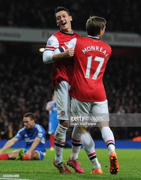 Mesut Ozil celebrates scoring the 2nd Arsenal goal with Nacho Monral during the match at Emirates Stadium on December 4 2013 in London England