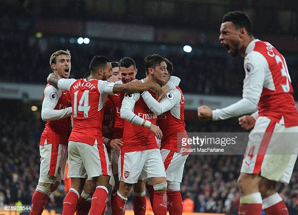 Mesut Ozil celebrates scoring the 2nd Arsenal goal with Nacho Monreal and Theo Walcott during the Premier League match between Arsenal and Stoke City...