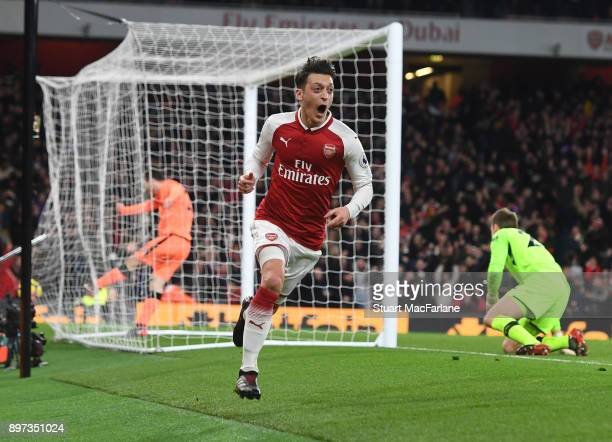 Mesut Ozil celebrates scoring the 3rd Arsenal goal during the Premier League match between Arsenal and Liverpool at Emirates Stadium on December 22...
