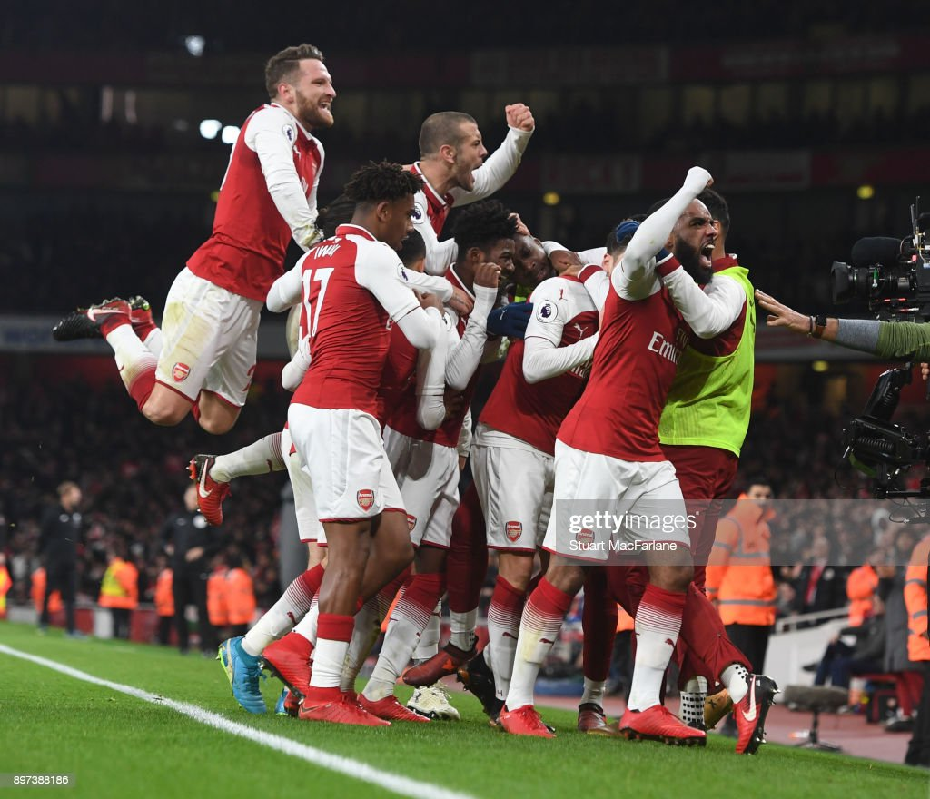 Mesut Ozil celebrates scoring the 3rd Arsenal goal with (R) Alex Lacazette (L) Shkodran Mustafi (2ndL) Hector Bellerin (3rdL) Jack Wilshere and (4thL) Alex Iwobi during the Premier League match between Arsenal and Liverpool at Emirates Stadium on December 22, 2017 in London, England.