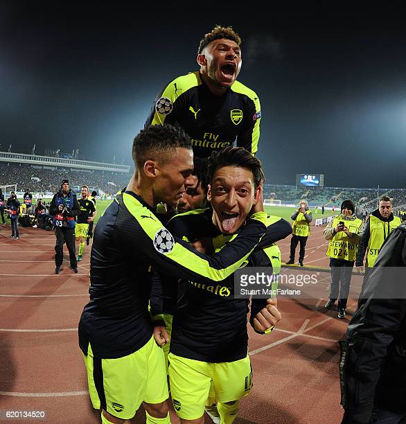 Mesut Ozil celebrates scoring the 3rd Arsenal goal with Kieran Gibbs Mohamed Elneny and Alex OxladeChamberlin during the UEFA Champions League match...
