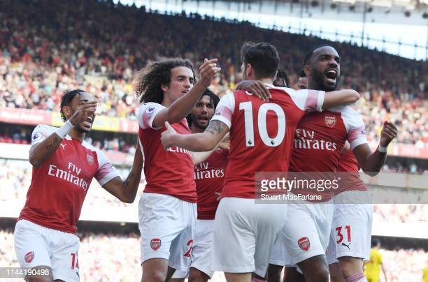 Mesut Ozil celebrates scoring the Arsenal goal with PierreEmerick Aubameyang Matteo Guendouzi and Alex Lacazette during the Premier League match...